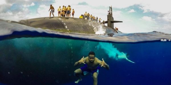 Check out these stunning photos of sailors swimming next to their nuclear submarine