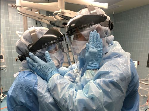 Through layers of protective gear, a married nurse couple shared a tender moment while tending to coronavirus patients at a busy Florida hospital